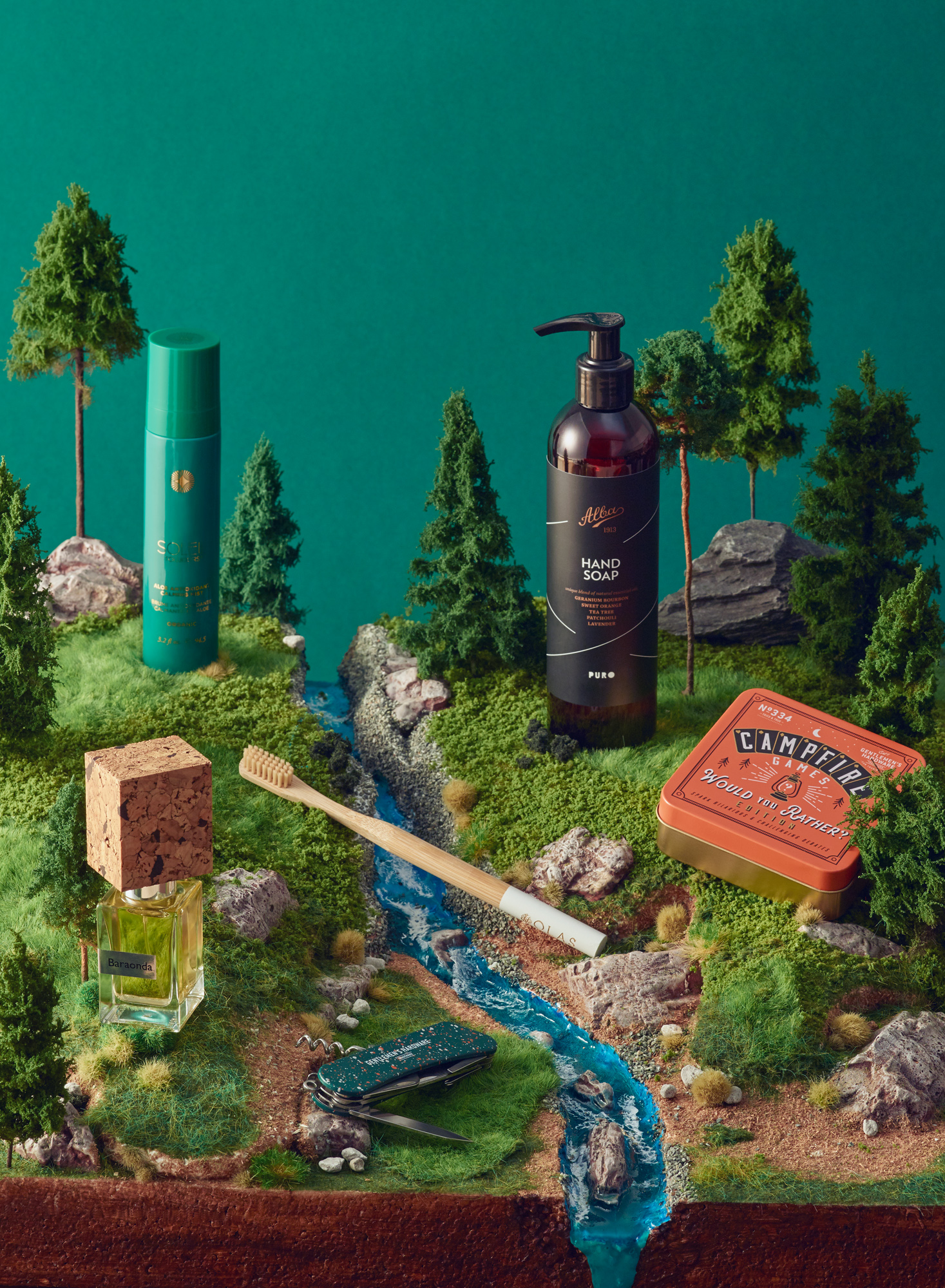 Still life photograph on diorama with comestics, toothbrush, perfume, Campfire Games. Usta Magazine Travel Issue