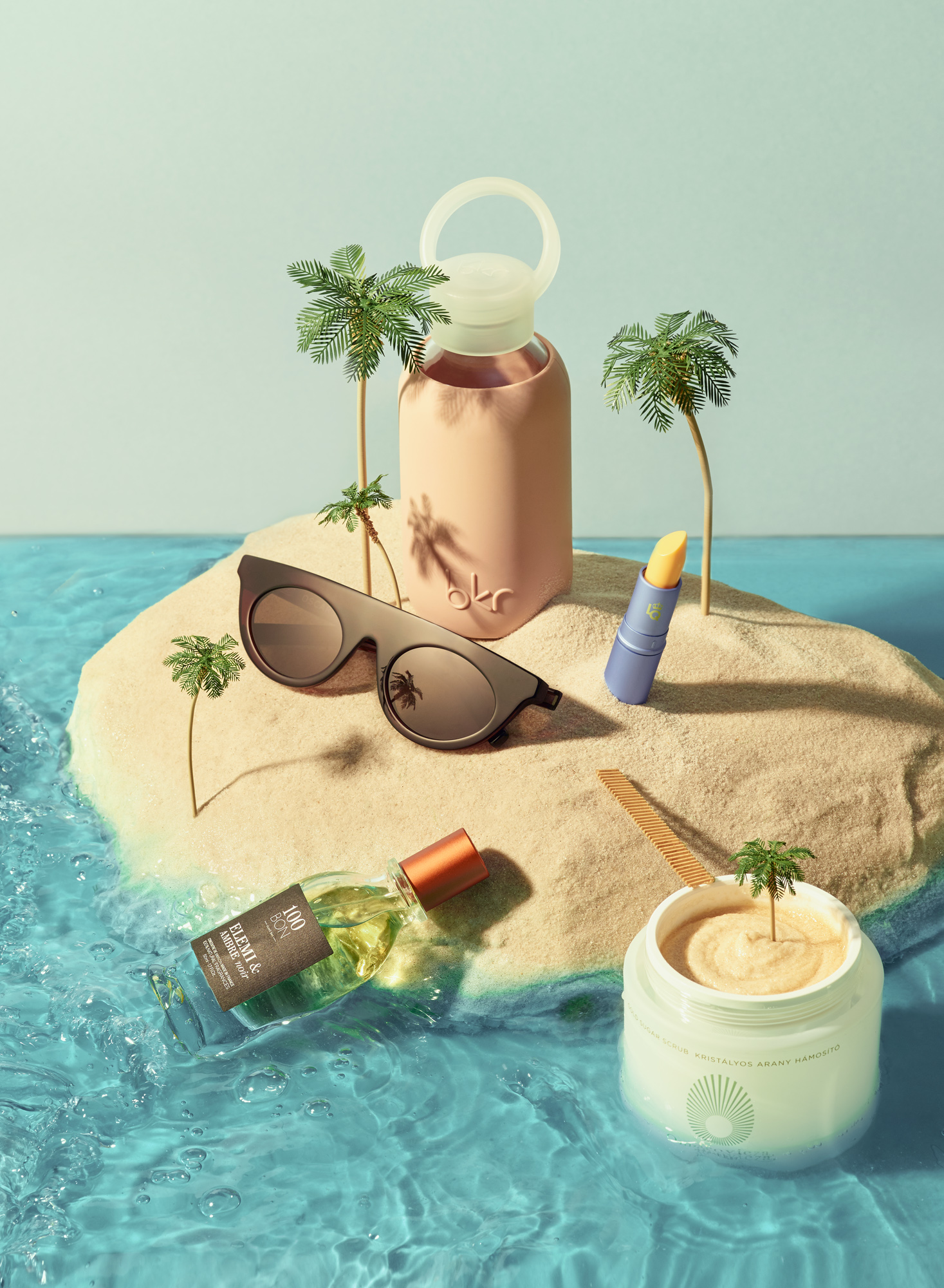 Still life photograph on Island Diorama with sunglasses, bottle, cream, lipstick and perfume