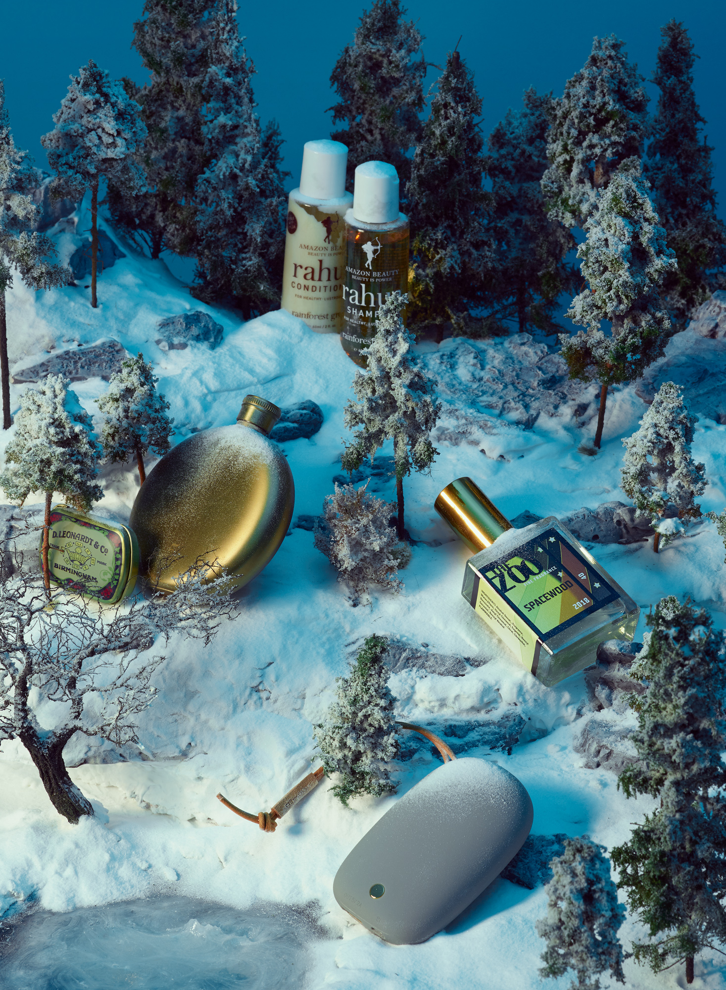 Still life on a winter diorama with Cosmetics, perfume, bottle and phone charger. Usta Magazine Travel Issue