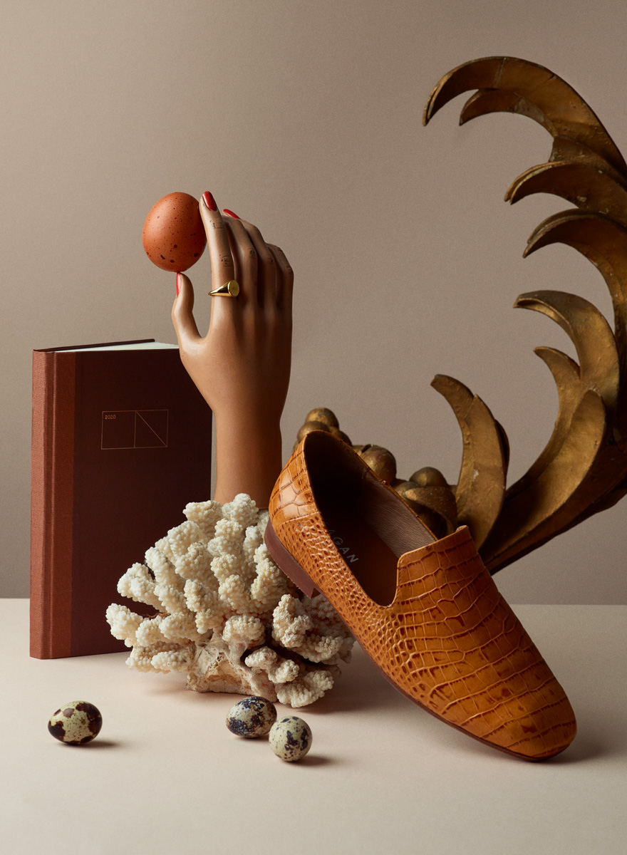 Still life photograph with loafer, hand, ring, egg and notebook