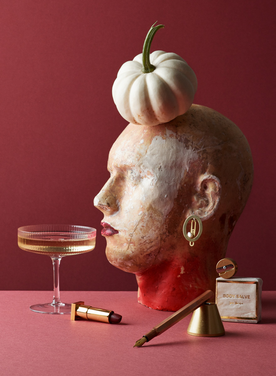 Still life with sculpture head, pumkin, Ferm Living chamapgne glass, lipstic, fountain pen, soap for USTA Magazine